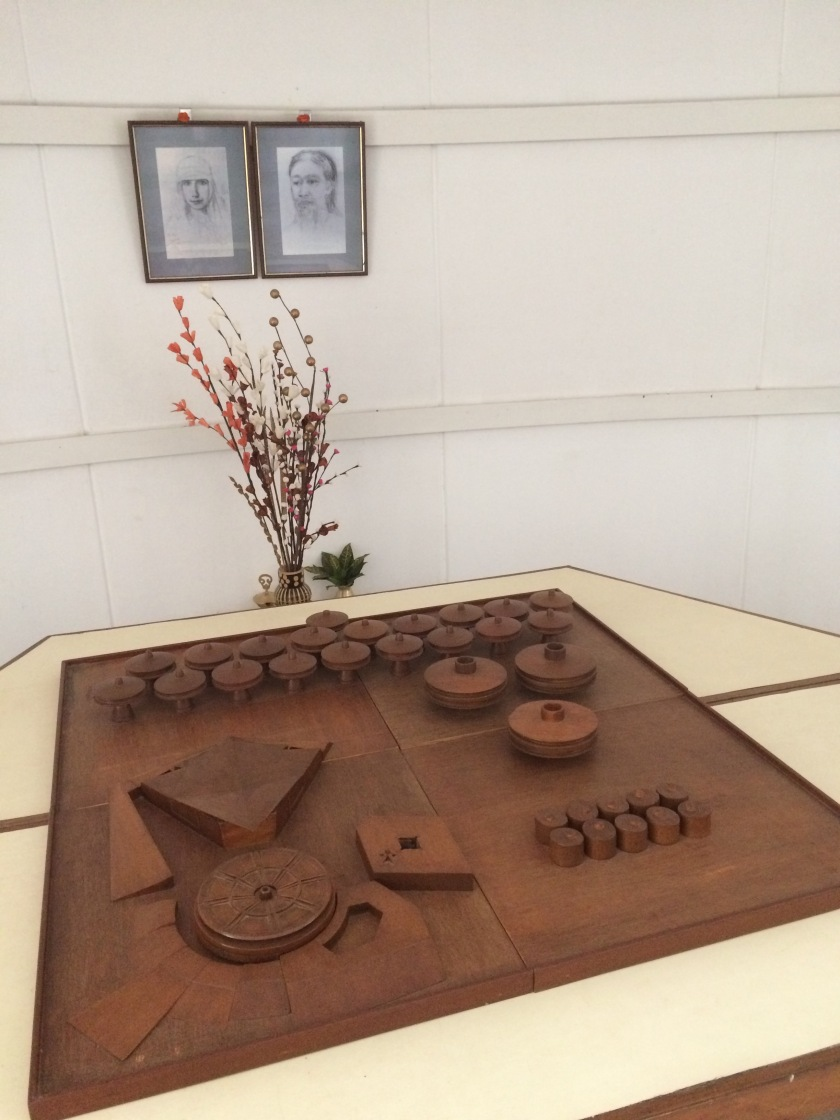 Portraits of Sri Aurobindo and The Mother above a model of the Matrimandir complex